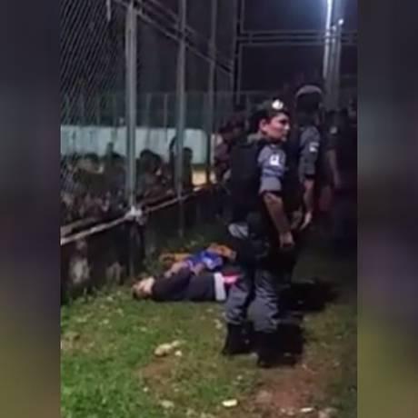 Policiais militares no campo de futebol onde seis foram mortos Foto: Reprodução