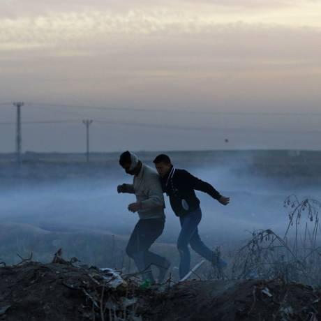 Manifestantes palestinos correm para se proteger de gás lacrimogêneo lançado por forças israelenses na fronteira de Gaza Foto: MOHAMMED ABED / AFP