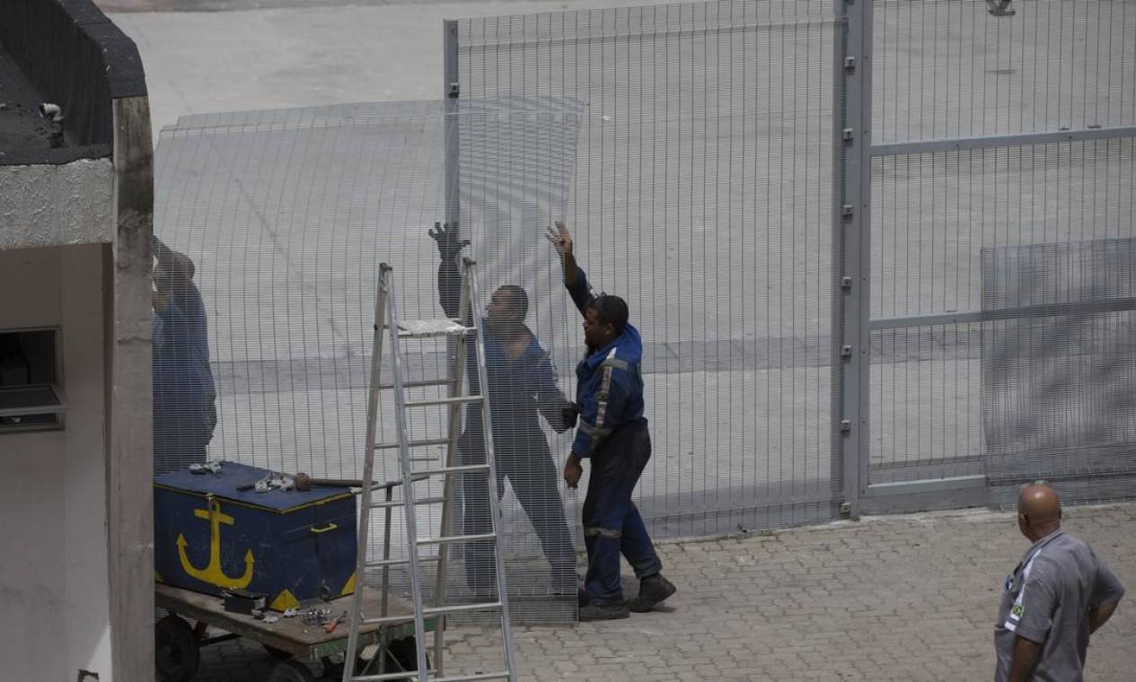 Funcionários tentam instalar uma nova grade no entorno do Maracanã Foto: Alexandre Cassiano / Alexandre Cassiano