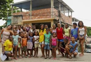 Ana Paula (de amarelo, ao centro) com as crianças atendidas pela ONG, que acaba de mudar de endereço Foto: Marcelo de Jesus