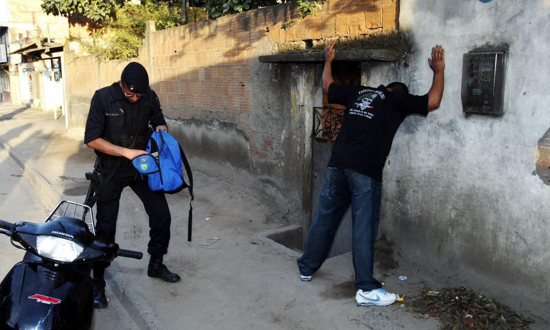 Policial revista homem durante operação; foto 10.08.2007 Foto: Celso Meira / Agência O Globo