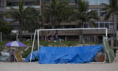 Aproveitando trave de jogo de futebol, grupo instala lona na Praia de Ipanema: entre os sem-teto, há empregados de barracas que ficam na orla para economizar com passagem Foto: Agência O Globo / Márcia Foletto