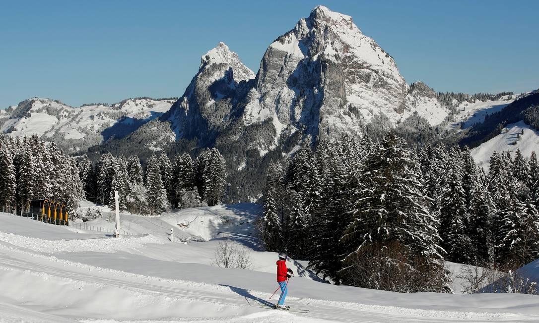 Um esquiador passa por trilha na neve no monte Grosser Mythen, enquanto o novo funicular é visto ao longe, no canto da foto: paisagem coberta de branco no início do inverno suíço Foto: ARND WIEGMANN / REUTERS