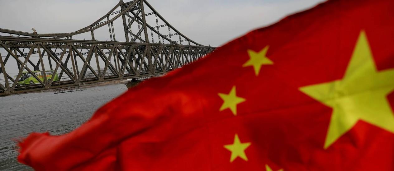 Bandeira chinesa tremula em frente à Ponte da Amizade sobre o Rio Yalu, conectando a cidade norte-coreana de Sinuiju e a chinesa Dandong, na província de Liaoning Foto: Damir Sagolj / REUTERS