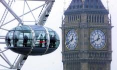 Turistas numa das gôndolas da London Eye, roda-gigante de Londres, com vista para o famoso Big Ben, no Palácio de Westminster Foto: Toby Melville / AP