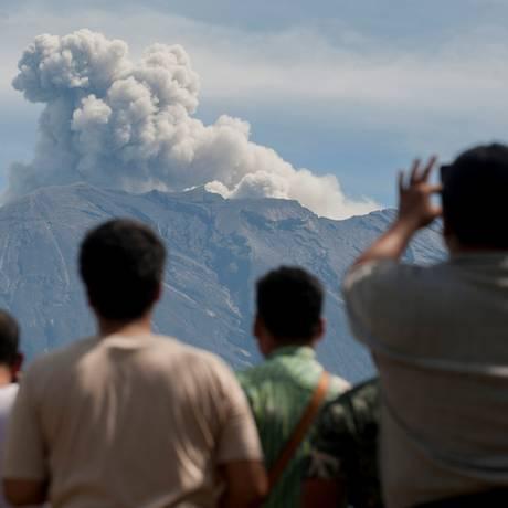 Turistas observam de muito longe, em Rendang, na Ilha de Bali, as nuvens de cinzas expelidas pelo vulcão do Monte Agung. A atividade vulcânica tem causado preocupação ao setor turístico da Indonésia Foto: ANTARA FOTO / REUTERS