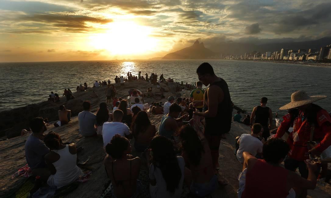 Cariocas e turistas se amontoam na Pedra do Arpoador para assistir ao sol se pôr entre as ilhas Tijucas: alto astral que é a cara do verão Foto: Agência O Globo / Márcio Alves
