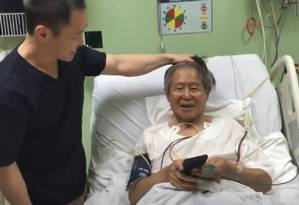 Fujimori lê no celular do filho, Kenji, o anúncio de seu indulto humanitário: livre após condenações Foto: Reprodução/Twitter