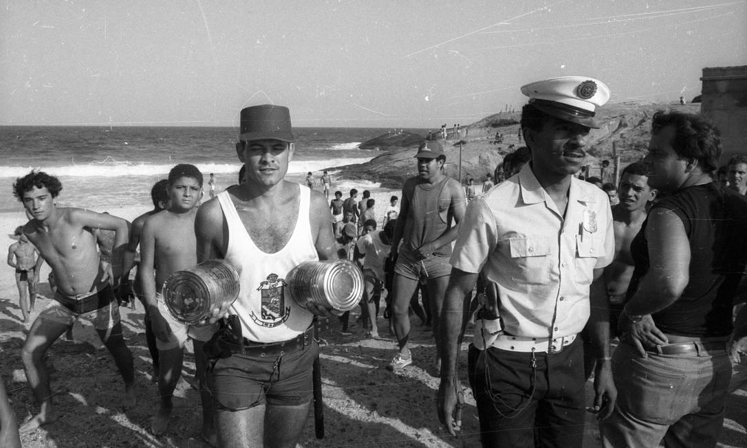 Policiais recolhem latas encontradas por banhistas em Ipanema, na Zona Sul do Rio Foto: Lúcio Marreiro / Arquivo O Globo (11/10/1987)