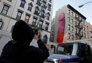 Homem fotografa o mural com um pênis gigante pontado num edifício em Nova York Foto: ANDREW KELLY / REUTERS