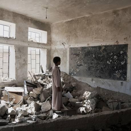 Estudante observa as ruínas da sala de aula onde estudava, em Saada, no Iêmen Foto: © UNICEF/UN073959 / Giles Clarke for UNOCHA