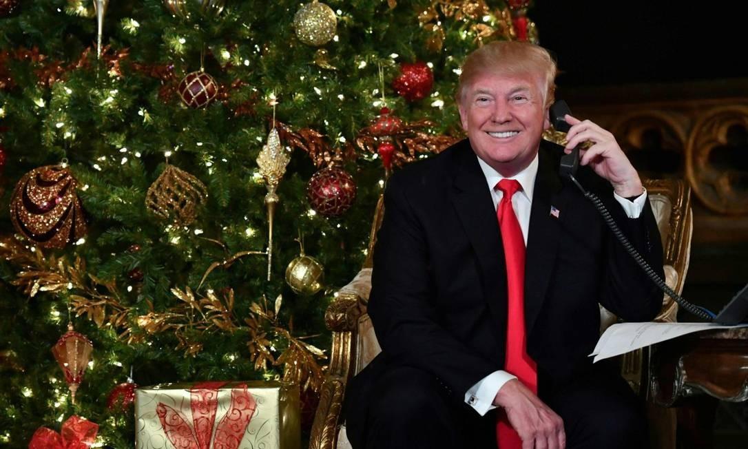 Donald Trump fala ao telefone na sua primeira véspera de natal como presidente dos EUA Foto: NICHOLAS KAMM / AFP