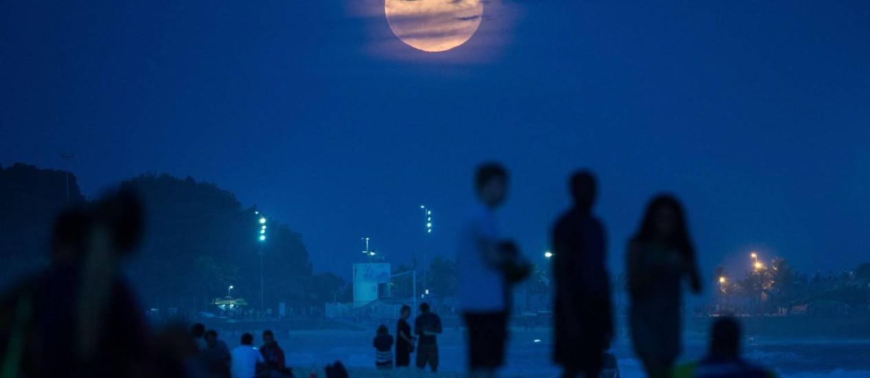Especialista recomenda que interessados em observar o fenômeno busquem locais de onde seja possível ver a Lua surgir no horizonte, como a praia de Ipanema, no Rio Foto: AFP/YASUYOSHI CHIBA/10-08-2014