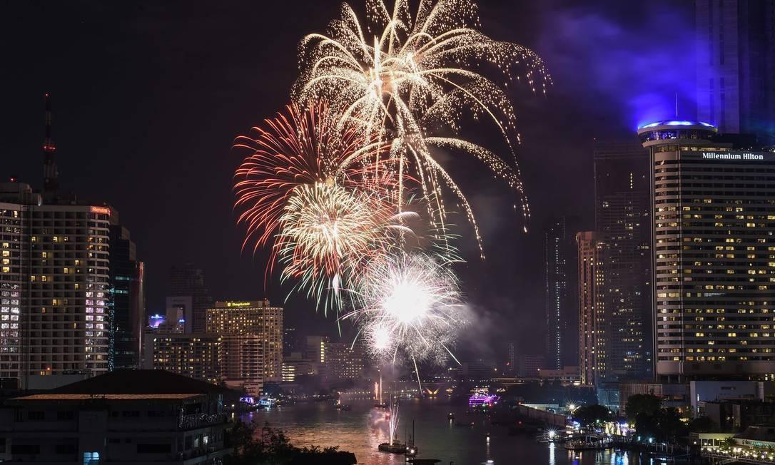 Uma exibição de fogo de artifício é vista sobre o rio Chao Phraya durante as celebrações de Ano Novo em Bangkok LILLIAN SUWANRUMPHA / AFP
