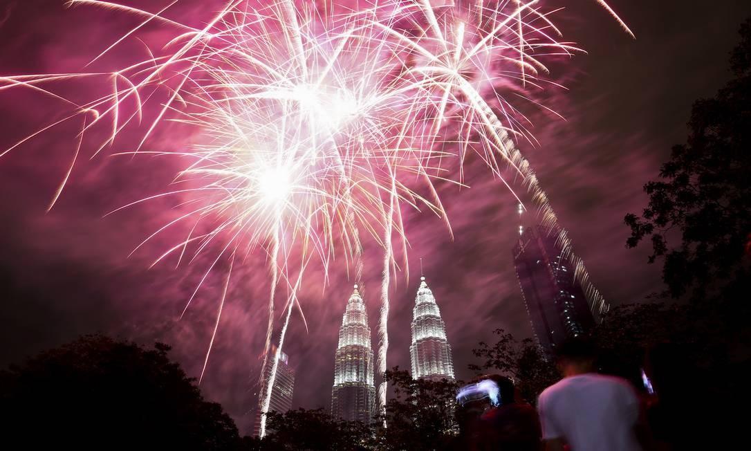 As pessoas vêem uma exibição de fogos de artifício em frente ao edifício histórico da Malásia, as Petronas Twin Towers, durante a celebração do Ano Novo em Kuala Lumpur. Sadiq Asyraf / AP