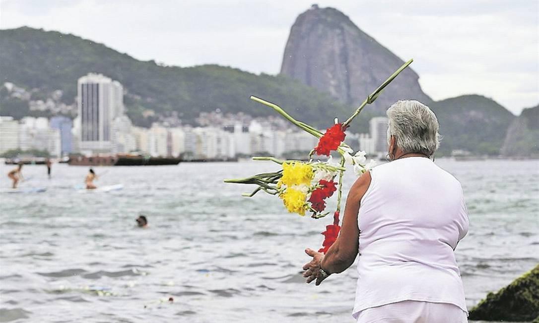 Mulher joga flores no mar, em Copacabana, no último dia do ano: pedidos de emprego, saúde e generosidade Foto: Guilherme Pinto / Agência O Globo
