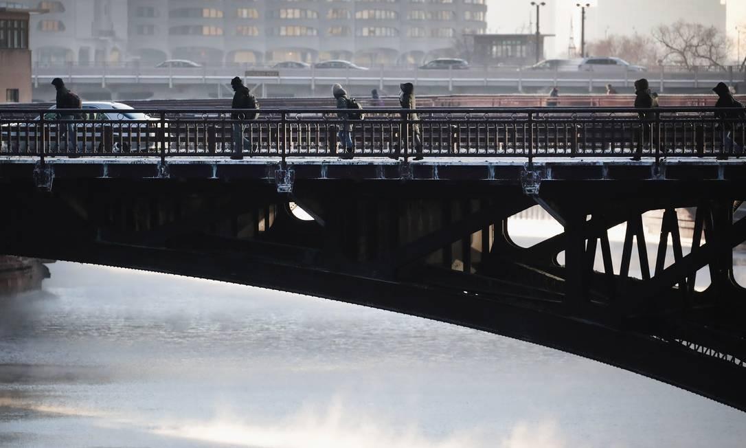 Pedestres enfrentam o frio cruzando a ponte do Rio Chicago. A cidade mais populosa de Illinois registra temperaturas abaixo de zero neste início de ano Foto: SCOTT OLSON / AFP