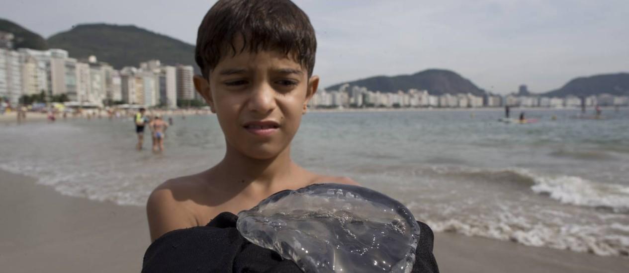 O menino Cássio Ferreira, de 9 anos, mostra a água-viva que encontrou no Posto 6, em Copacabana Foto: Márcia Foletto / Agência O Globo