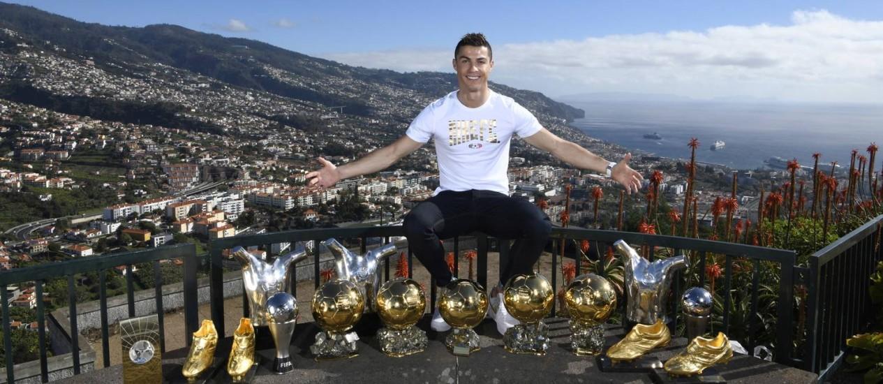 Cinco vezes eleito melhor jogador do mundo, Cristiano Ronaldo posa em Funchal, Ilha da Madeira, com 15 de seus troféus mais importantes. A terra onde ele nasceu tem um Hotel CR7, marca do jogador que terá unidades também em Marrakech, Madri e Nova York, além de outra que já existe em Lisboa Foto: HO / AP