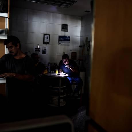 Funcionários de uma companhia de distribuição de alimentos usam seus celulares para trabalhar durante um apagão que acometeu Caracas, na Venezuela, no último 18 de dezembrou Foto: JUAN BARRETO / AFP
