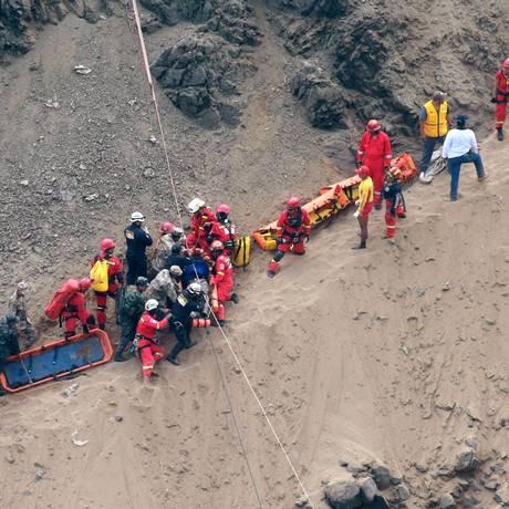 Socorristas cercam um homem ferido após ônibus cair em abismo em Pasamayo, Peru Foto: Vidal Tarky / AP
