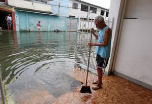 Salvador tenta retirar o esgoto que entra em sua casa. Ele e a mulher estão ilhados Foto: Fabiano Rocha / Agência O Globo