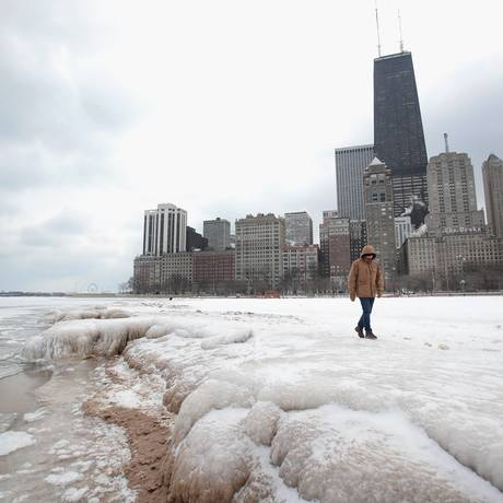 Homem caminha por uma Chicago completamente coberta de neve causada pela