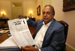 Pezão e sua lista de promessas assinada, ainda sem contar com a crise que esperava por ele nos anos seguintes Foto: Ivo Gonzalez / O Globo (27/10/2014)