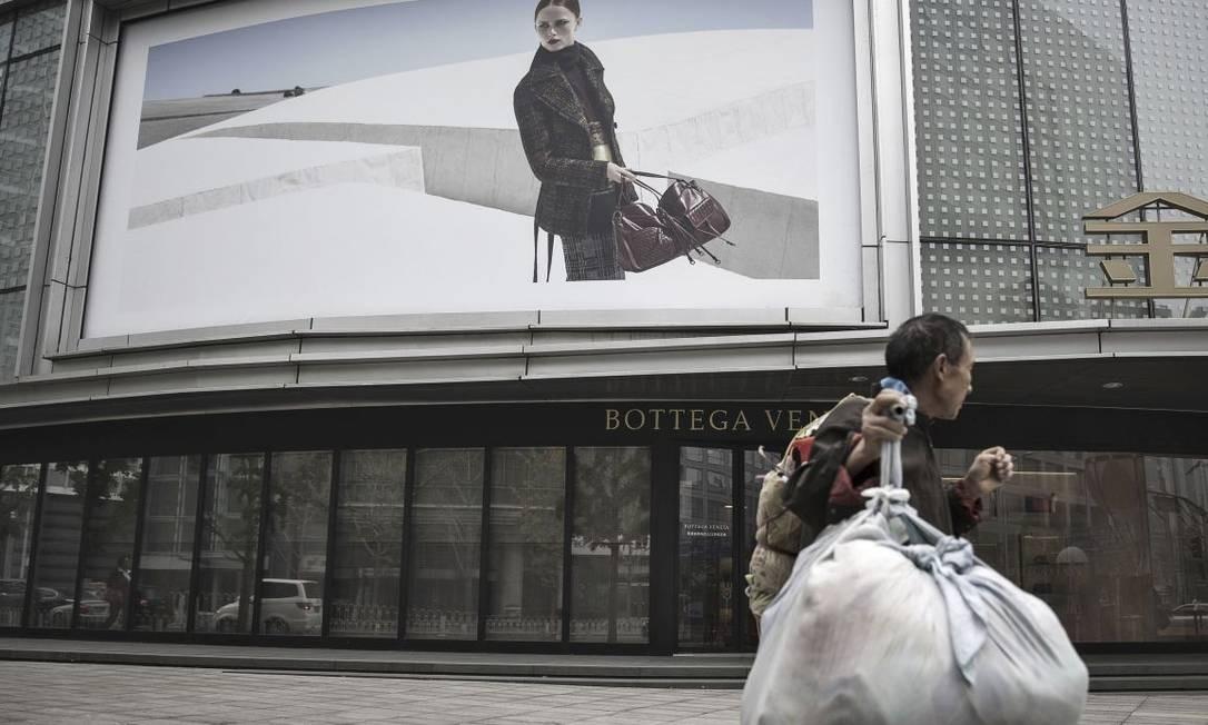 Homem com saco de bambu em frente a um shopping em Pequim: trabalho informal é alternativa Foto: Qilai Shen / Bloomberg