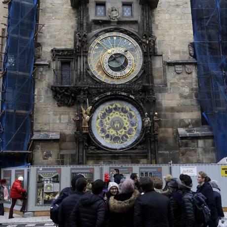 Turistas se reúnem em frente ao relógio astronômico de Praga, na República Tcheca: a atração parou de funcionar para ser restaurada, e a obra deve levar meses Foto: Petr David Josek / AP