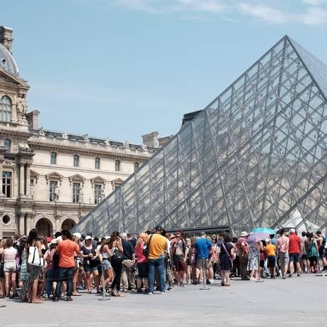 Turistas fazem fila para entrar no Louvre, no verao parisiense: mais de oito milhões de visitantes foram ao museu em 2017 Foto: MIGUEL MEDINA / AFP