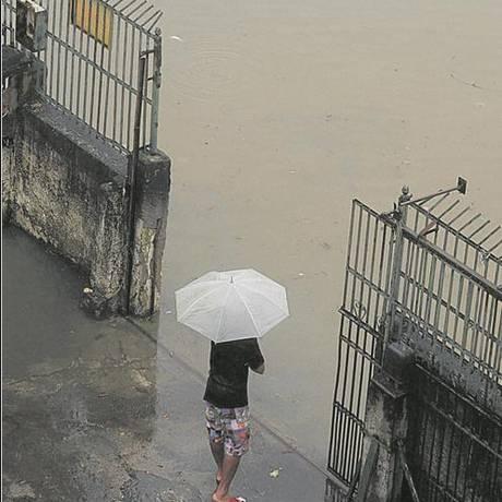 Longe de uma solução. Um morador vê o Rio Acari tomar a rua em frente à sua casa: chuva durante toda a madrugada de ontem deixou população ilhada na região Foto: Fabiano Rocha / Agência O Globo