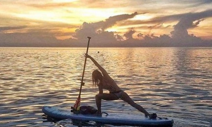 Diante de um lindo céu, praticante de stand up paddle faz alongamento no Lago Ontario, no Canadá Foto: Paddle Niagara / divulgação