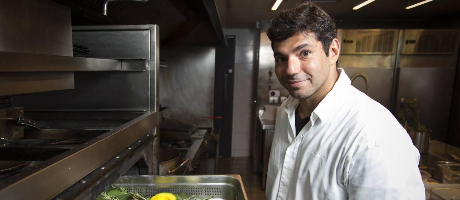 O chef Felipe Bronze, na cozinha do Pipo, com assadeira em mãos antes de defumar o abacate com louro, tomilho e alecrim Foto: Leo Martins / Agência O Globo