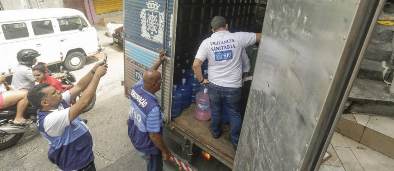 Agentes da Vigilância Sanitária recolhem galões de água numa distribuidora no Morro do Vidigal, que foram levados para um depósito da prefeitura Foto: Gabriel de Paiva / Agência O Globo