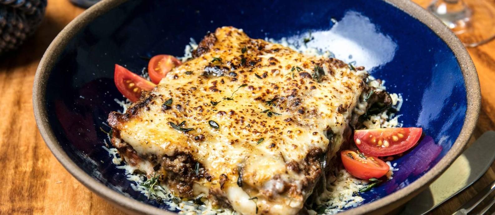 O mais tradicional dos pratos gregos, moussaka (no Vokos): finas fatias de berinjela, batata com ragout de carne e molho bechamel Foto: Divulgação/Tomas Rangel