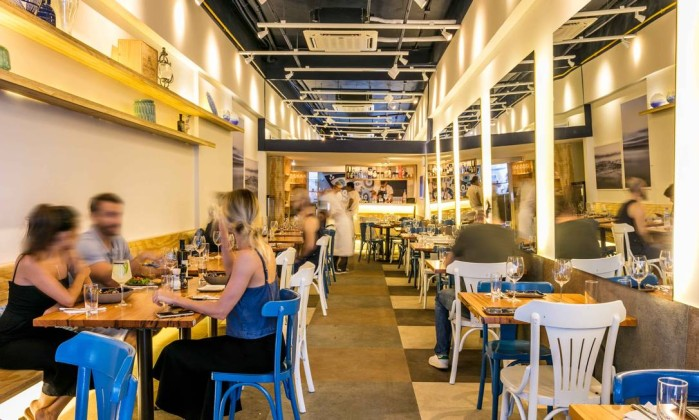 O salão tem 55 lugares, mesas de madeira clara e cadeiras em azul e branco Foto: Divulgação/Tomas Rangel