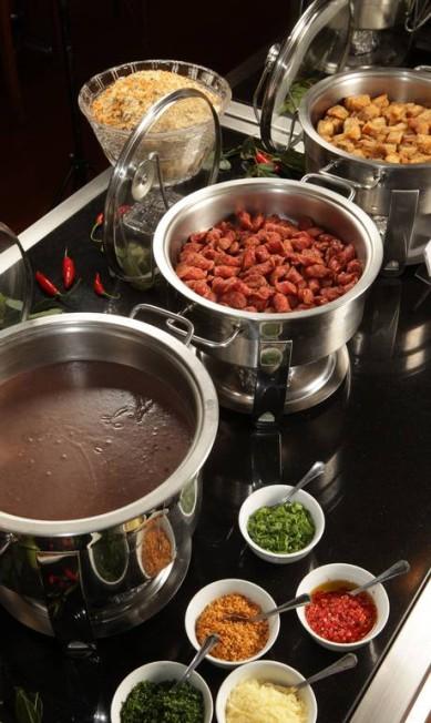 O Chef Marcones Deus oferece todos os sábados, do meio-dia às 17h, feijoada em bufê no Victoria (R$ 76, adulto, e R$ 28, crianças até 12 anos). De entrada, tem caldinho de feijão com salsinha, cebolinha, queijo ralado, bacon e pimenta. Para acompanhar, arroz, couve, purê de abóbora, farofa crocante de cebola roxa, torresmo, linguiçinha frita e carne-seca acebolada. Entre as opções de carnes, lombinho ao molho sálvia e limão, paio, linguiça, costelinha, lombo, carne-seca e língua defumada. Rua Mário Ribeiro 410, Lagoa (2540-9017). Divulgação/Berg Silva