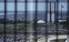 Vistos de longe e atrás das grades, o Congresso e o Palácio do Planalto são símbolos das instituições brasileiras que deveriam, com o Judiciário, impedir a apropriação do Estado por interesses particulares Foto: André Coelho / Agência O Globo