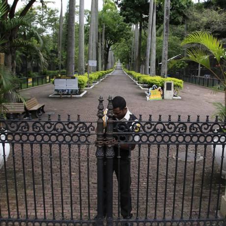 Funcionário tranca a porta do Zoológico, após tiroteios na Mangueira Foto: Uanderson Fernandes