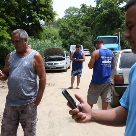 O distrito de Cabuçu, em Itaboraí, é um dos 2.000 distritos do país que não contam cobertura de celular. Valdir Batista (mais velho) e Danilo Santos (direita) tentam conseguir sinal Foto: Custódio Coimbra