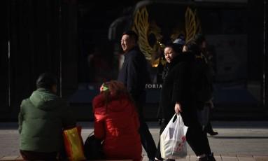 Chineses caminham em loja de comércio em Pequim. Foto: Wang Zhao/AFP