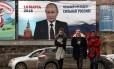 Pedestres passam em frente a imagem do presidente russo, Vladimir Putin, em Simferopol, na Crimeia Foto: STR / AFP