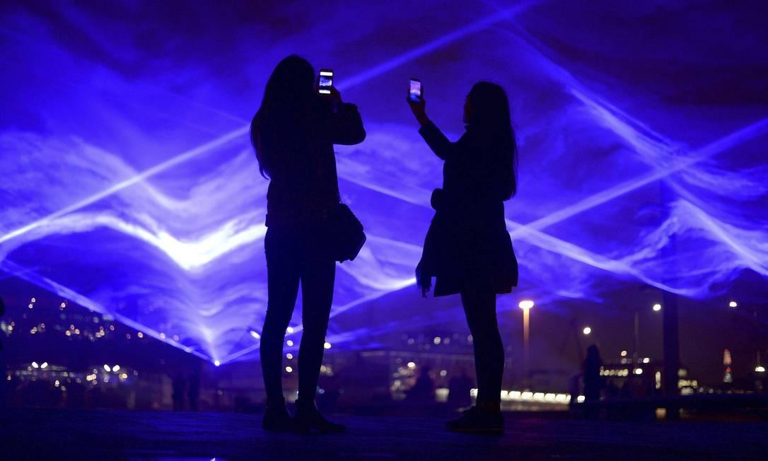"""Duas pessoas tiram fotos das luzes na Granary Square, em Londres, atração do festival de luzes Lumiere. A obra """"Waterlicht"""" é uma criação de Daan Roosegaarde Foto: Kirsty O'Connor / AP"""