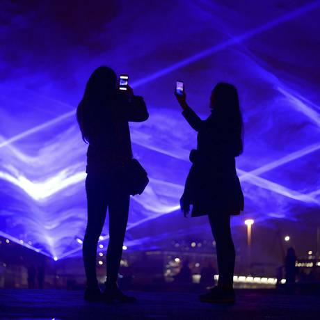 Duas pessoas tiram fotos das luzes na Granary Square, em Londres, atração do festival de luzes Lumiere. A obra