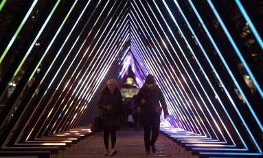 """Pessoas caminham pela instalação """"The Wave"""", de Vertigo, parte do festival de luzes """"Lumiere"""" , em Londres Foto: JUSTIN TALLIS / AFP"""