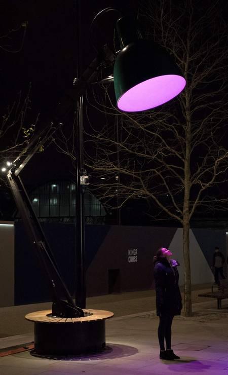 """A luz lilás da obra """"Lampounette"""", de Tilt, dá um colorido diferente a uma mulher. O festival """"Lumiere"""" interefere com luzes diferentes na paisagem do inverno londrino Foto: JUSTIN TALLIS / AFP"""
