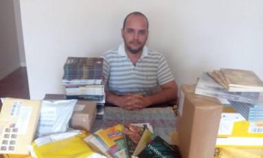 O professsor Leandro Garcia mostra os livros que já arrecadou na campanha Foto: Reprodução