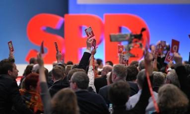 Delegados do SPD erguem cartões de votação dando aval a coalizão Foto: SASCHA SCHUERMANN / AFP