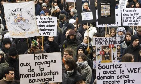 Protestos. Manifestantes carregam cartazes contra o Fórum Econômico Mundial, quatro meses após o início da crise global Foto: Valentin Flauraud 31/01/2009 / Reuters